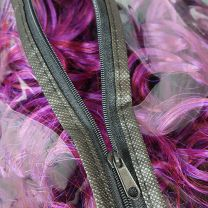 Zipper partly open and purple hair seen through clear plastic of hair extension storage bag